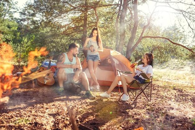 Feest, kamperen van mannen en vrouwengroep in het bos. ze ontspannen tegen groen gras. het concept van vakantie, zomer, avontuur, levensstijl, picknick
