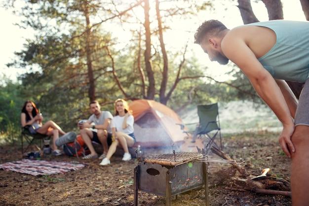 Feest, kamperen van mannen en vrouwengroep in het bos. ze ontspannen, zingen een lied en koken barbecue tegen groen gras. het concept van vakantie, zomer, avontuur, levensstijl, picknick