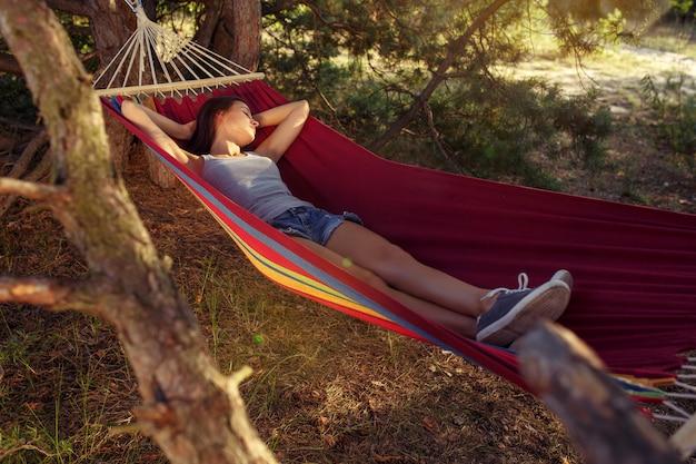 Feest, kamperen. vrouw slapen op bos. ze ontspant