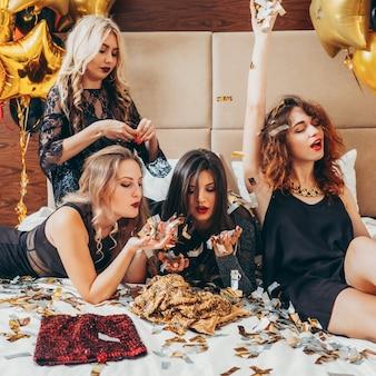 Feest meiden. plezier en vreugde. glitter confetti. jonge vrouwen in het zwart ontspannen op bed. feestelijke sfeer en inrichting