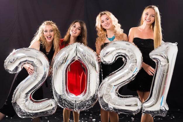 Feest, mensen en nieuwjaarsvakantieconcept - vrolijke jonge vrouwen die oudejaarsavond 2021 vieren