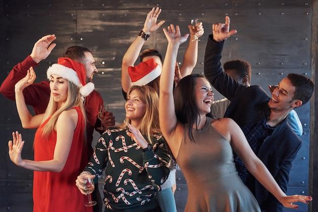 Feest met vrienden. ze houden van kerstmis. groep vrolijke jonge sterretjes en champagnefluiten die in nieuwe jaarpartij dansen en gelukkig kijken. concepten over samenhorigheid levensstijl