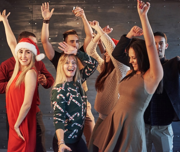 Feest met vrienden. ze houden van kerstmis. groep vrolijke jongeren die sterretjes en champagnefluiten dragen die in nieuwe jaarpartij dansen en gelukkig kijken. concepten over saamhorigheidsstijl