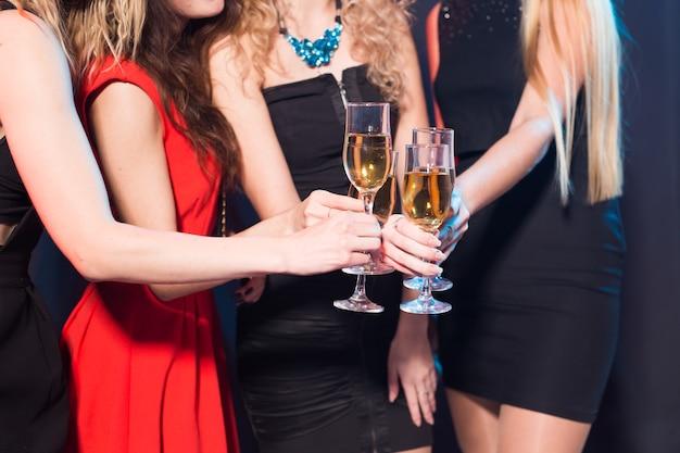 Feest, nieuwjaar en mensen concept - close-up van jonge vrouwen rammelende glazen champagne op het feest