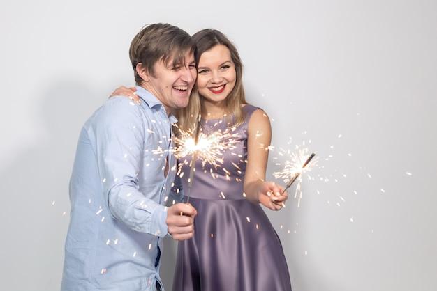 Feest, plezier, nieuwjaar, kerst en feestdagen concept - jong gelukkig stel met sterretjes op witte achtergrond