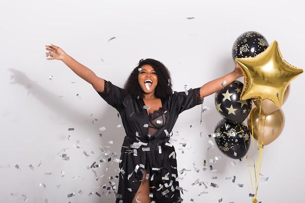 Feest, vakantie en verjaardag concept - geluk vieren, jonge vrouw dansen met een grote glimlach confetti gooien