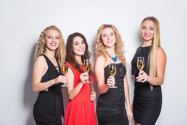 Feest, vakantie, feest en oudejaarsavond concept - vrolijke jonge vrouw rammelende glazen champagne op het feest.
