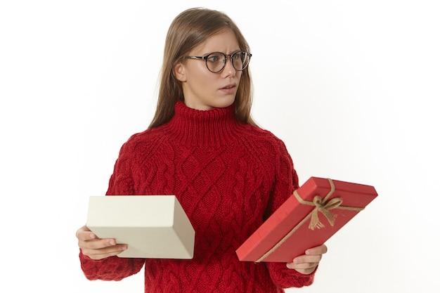 Feest, vakantie, geschenken, cadeautjes en speciale gelegenheden concept. foto van gefrustreerde jonge europese vrouw in warme trui en bril grijnzend van verontwaardiging, teleurgesteld met een slecht cadeau
