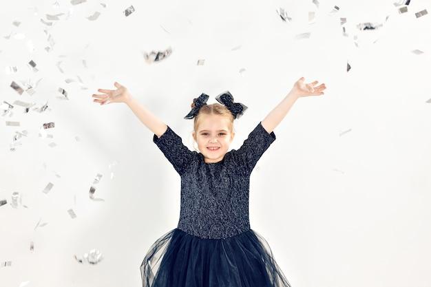 Feest, vakantie, nieuwjaar en vieringsconcept - vrouwelijk kind dat confetti gooit.