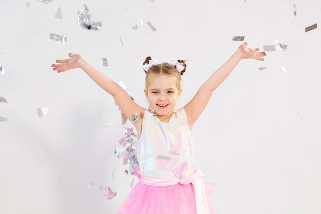 Feest, vakantie, verjaardag, nieuwjaar en vieringsconcept - schattig kind dat confetti gooit.