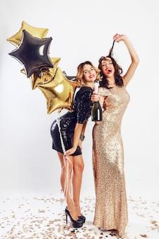 Feest van twee beste vrienden in elegante cocktailjurk poseren in studio op witte achtergrond. sprankelende gouden confetti. golvend kapsel. feest ballonnen.