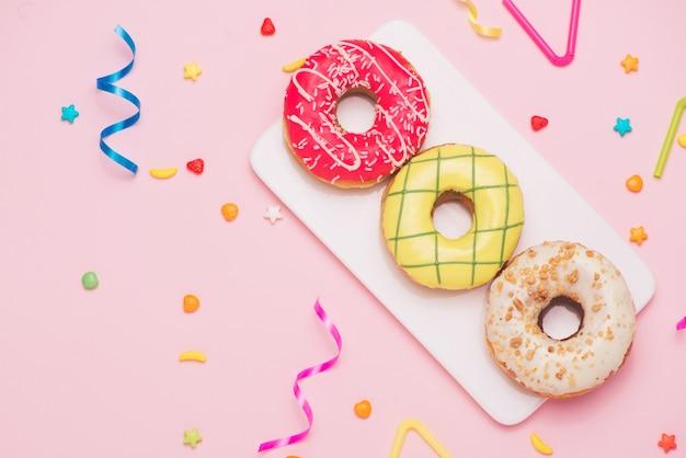 Feest. verschillende kleurrijke suikerachtige ronde geglazuurde donuts en flessen drankjes op roze achtergrond.