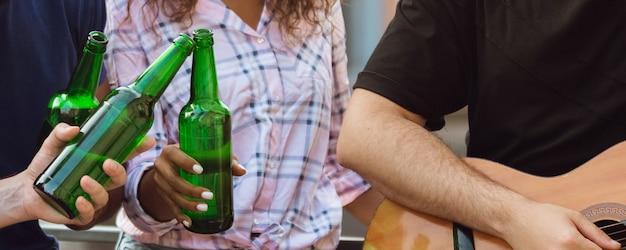 Feest vieren. handen van vrienden, collega's tijdens bier drinken, plezier maken, rammelende flessen, glazen samen.