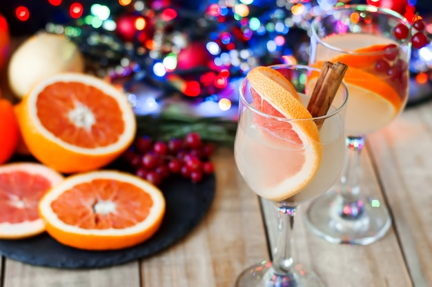 Feestcocktails met sinaasappel, grapefruit, kaneelstokjes en rode bessen
