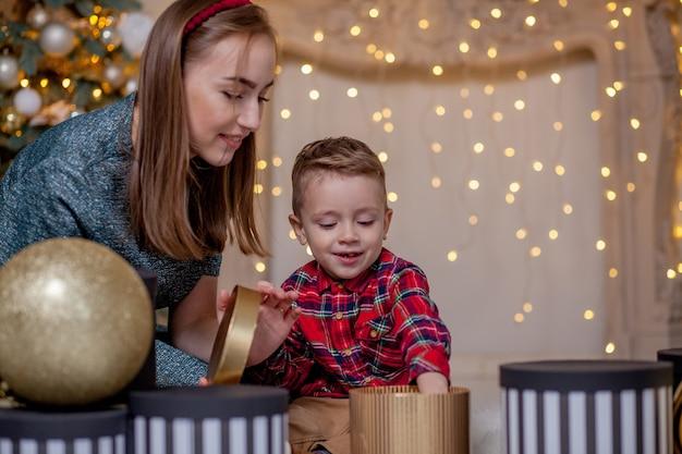 Feestdagen en cadeautjes concept - close-up van familie geschenken openen in de kersttijd.
