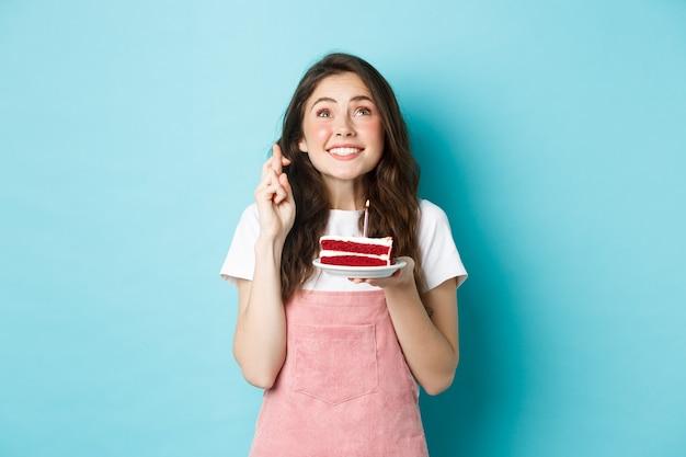 Feestdagen en feest. hoopvol jong meisje dat verjaardag viert, opkijkt en vingers kruist voor geluk, een wens doet op kaars in cake, staande over blauwe achtergrond.