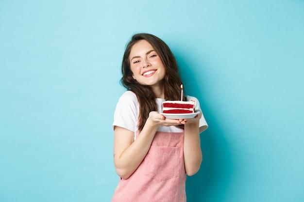 Feestdagen en feest. leuk glamourmeisje dat haar verjaardag viert, bord met cake vasthoudt en vrolijk lacht, viert, staande over blauwe achtergrond.