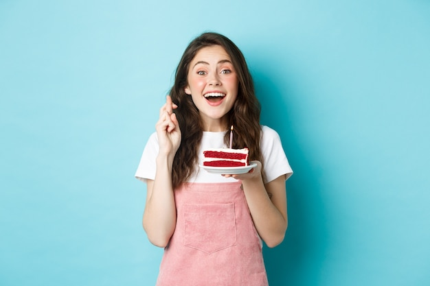 Feestdagen en feest. opgewonden vrouw die verjaardag viert, vingers kruist en een wens doet terwijl ze een kaars op een taart blaast, staande tegen een blauwe achtergrond