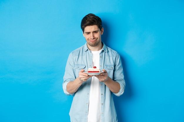 Feestdagen en feest. teleurgestelde en droevige man die naar verjaardagstaart kijkt, overstuur grijnst, staande tegen een blauwe achtergrond