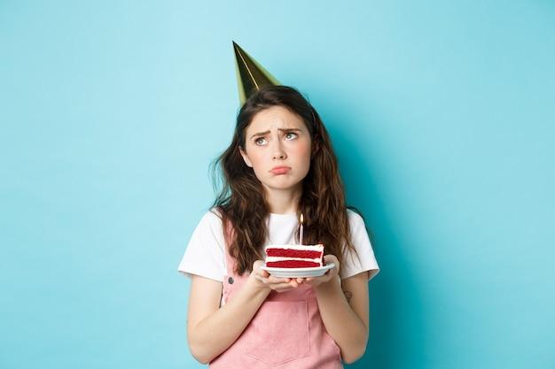 Feestdagen en feest. verdrietig meisje in feestmuts met verjaardagstaart, wegkijkend met een bedachtzame grimas, zich eenzaam en humeurig voelen op haar verjaardag, staande over blauwe achtergrond.