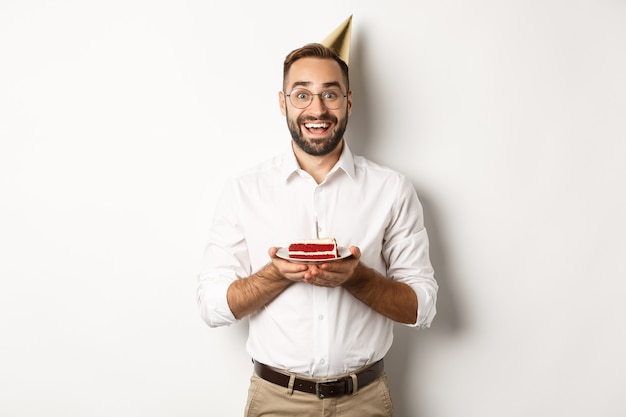 Feestdagen en feesten. gelukkig man met verjaardagsfeestje, wens maken op b-day cake en glimlachen, staan