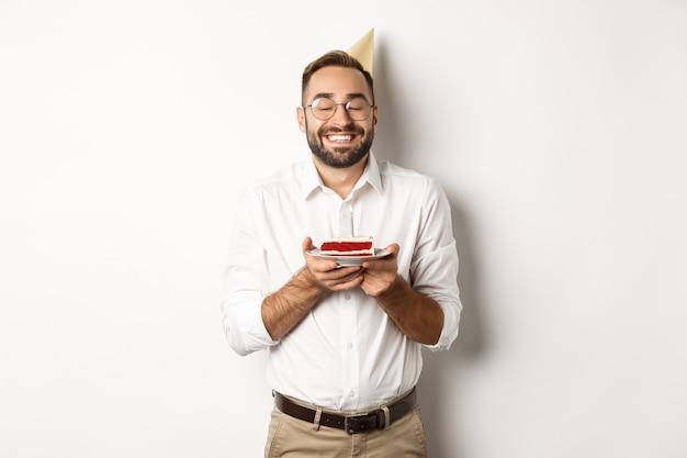 Feestdagen en feesten. gelukkig man met verjaardagsfeestje, wens maken op b-day cake en glimlachen, staande tegen een witte achtergrond.