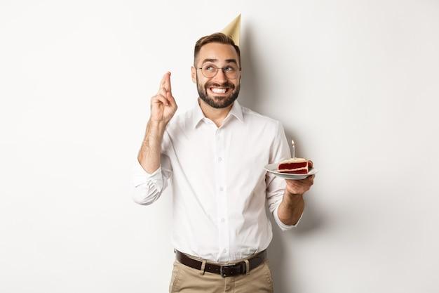 Feestdagen en feesten. gelukkig man met verjaardagsfeestje, wens maken op b-day cake en kruis vingers voor geluk, staande tegen een witte achtergrond.
