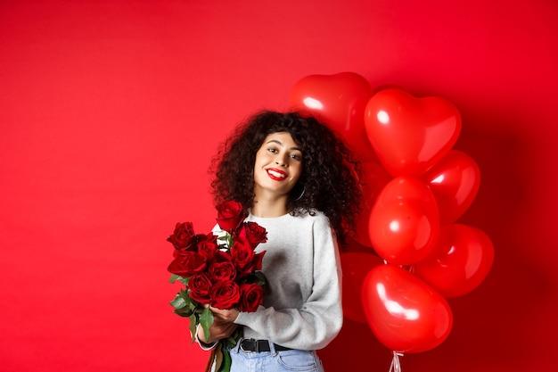 Feestdagen en feesten. gelukkig mooie vrouw met krullend haar, boeket rozen ontvangen en glimlachen, staande in de buurt van feestballonnen, rode achtergrond.