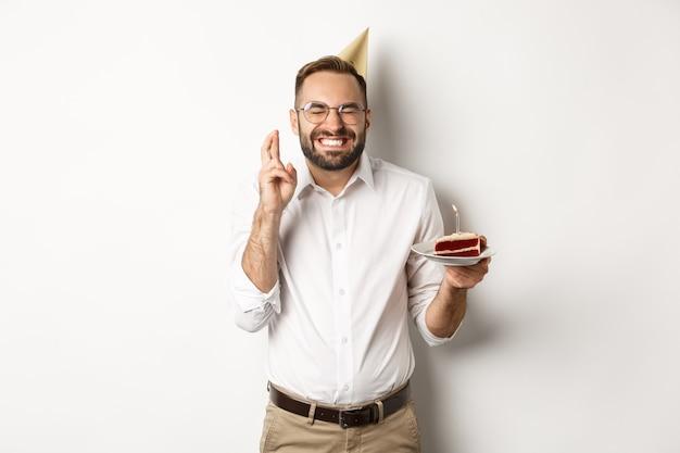 Feestdagen en feesten. gelukkige mens die wens op verjaardagstaart maakt, kruis vingers en opgewonden glimlachend, die b-dagpartij, witte achtergrond hebben.