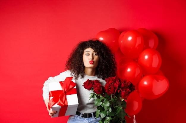Feestdagen en feesten. mooie vrouw viert verjaardag waait luchtkus, ontvangt geschenken en bloemen op verjaardag, staande in de buurt van feestballonnen, rode muur.