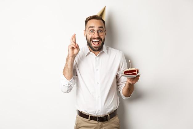 Feestdagen en feesten. opgewonden man met verjaardagsfeestje, wens op b-day cake en kruis vingers voor geluk, staande tegen een witte achtergrond.