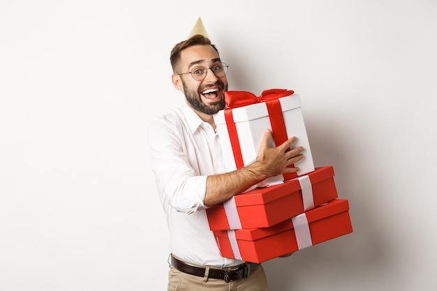 Feestdagen en feesten. opgewonden man verjaardagsfeestje hebben en geschenken ontvangen, op zoek gelukkig, staande op witte achtergrond.