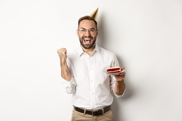 Feestdagen en feesten. verjaardagsfeestje die wens doet op verjaardagstaart en zich verheugt, vuistpomp teken maakt als winnende, doel bereikt