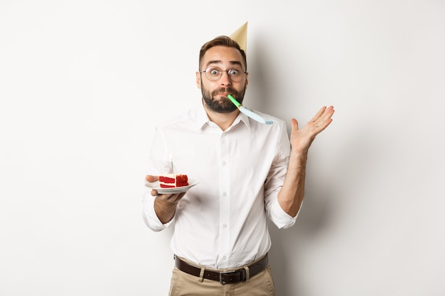 Feestdagen en feesten. vrolijke man genieten van verjaardag, partij fluitje blazen en bday cake, witte achtergrond te houden.