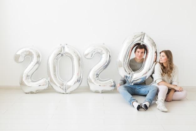 Feestdagen, feestelijk en feest concept - grappig paar zittend op een vloer in de buurt van zilveren 2020 ballonnen. nieuwjaarsviering