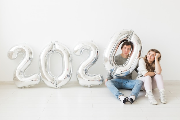 Feestdagen, feestelijk en feest concept - happy verliefde paar zittend op een vloer in de buurt van zilveren 2020 ballonnen nieuwjaarsviering