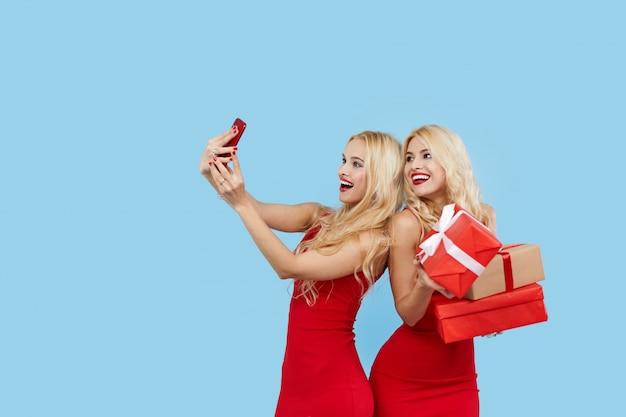 Feestdagen verkoop. gelukkige vrouwen met geschenkdozen in rode jurken, maakt selfie op smartphone.