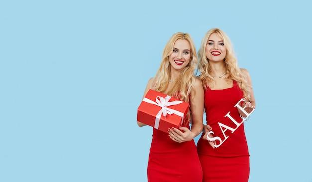 Feestdagen verkoop. gelukkige vrouwen met geschenkdozen in rode jurken