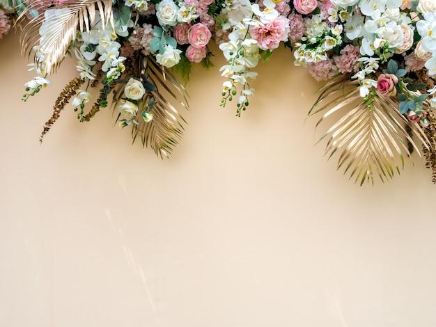 Feestdecoratie met gouden tropische palmbladeren met witte en roze rozen bloemboeket.