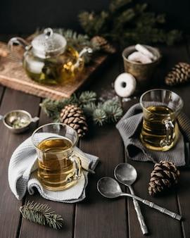 Feestelijk arrangement met hoge hoek met thee en dennenappels