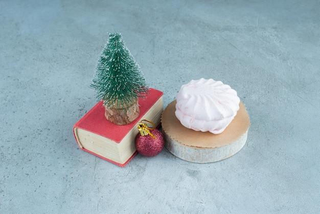 Feestelijk arrangement van een kerstbal, een boomfiguur op een boekje en gestapelde koekjes op marmer.