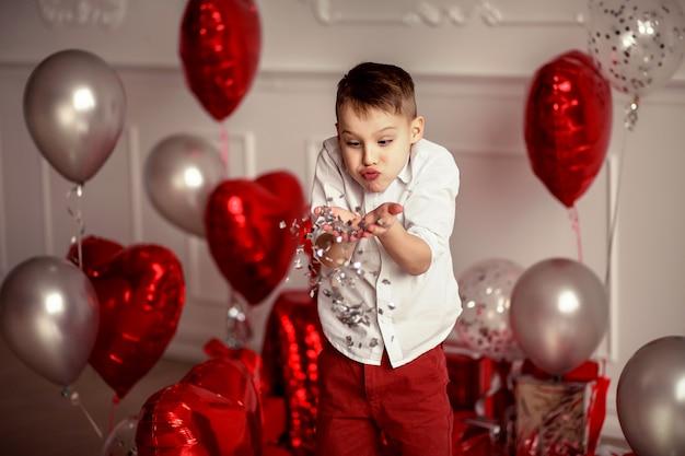Feestelijk decor voor een verjaardag of valentijnsdag. ballonnen in de vorm van grote rode harten en confetti. vrolijke kind jongen blaast en gooit confetti