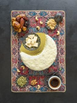 Feestelijk eten ramadan achtergrond. heerlijke zelfgemaakte cake in de vorm van een halve maan, geserveerd met dadels en koffiekopje