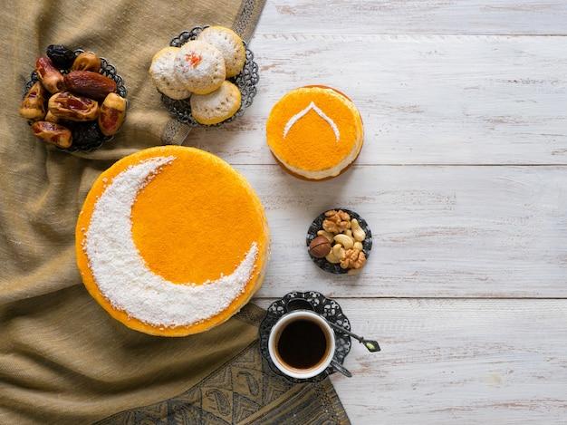 Feestelijk eten ramadan muur. heerlijke zelfgemaakte gouden cake met een halve maan, geserveerd met zwarte koffie en dadels. bovenaanzicht.