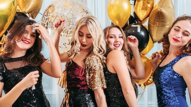 Feestelijk feest voor meisjes. geamuseerde dames in cocktailjurken met lovertjes die genieten van tijd samen, plezier hebben, dansen over gouden ballonnen.