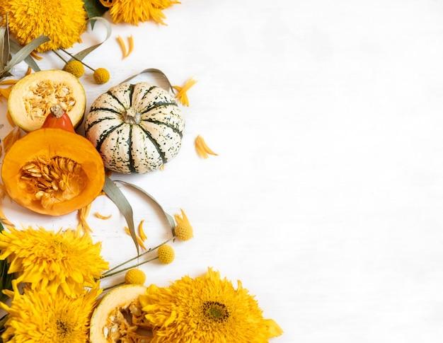 Feestelijk herfstdecor van pompoenen en bloemen op een witte achtergrond. concept van thanksgiving day of halloween. platliggende herfstcompositie met kopieerruimte.