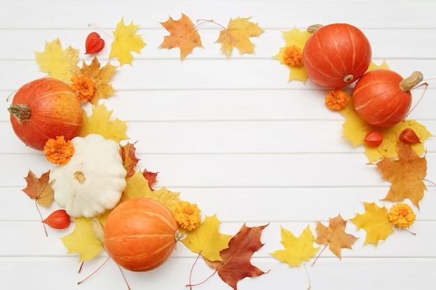 Feestelijk herfstdecor van pompoenen en esdoornbladeren op een witte houten ondergrond. concept van thanksgiving day of halloween. platliggende herfstcompositie met kopieerruimte.