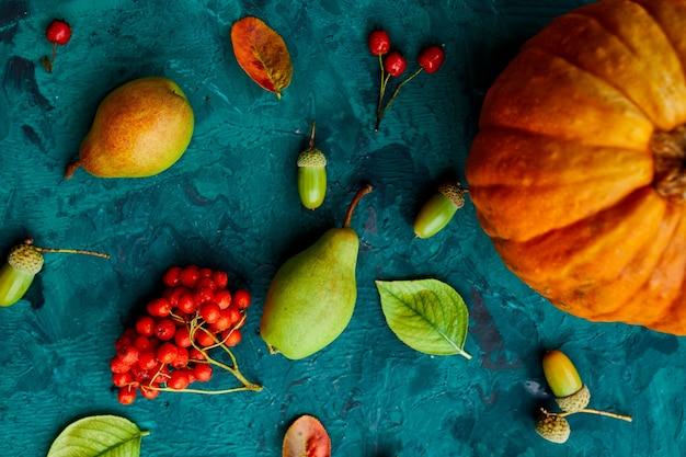 Feestelijk herfstdecor van pompoenen, peren, bladeren, eikels en bessen op groene achtergrond, herfst plat leggen, herfstsamenstelling, oogst, thanksgiving day.