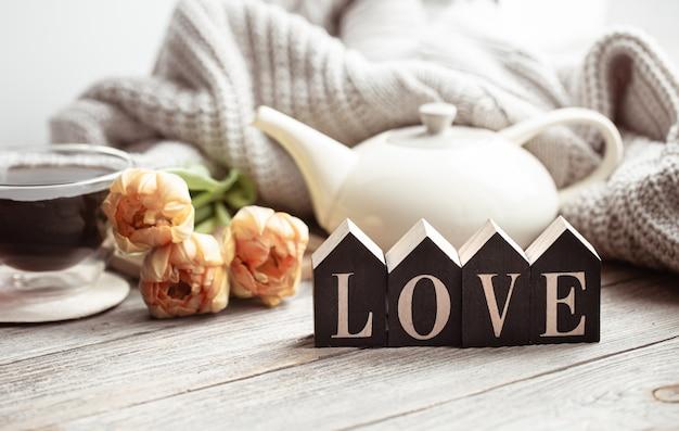 Feestelijk huisstilleven met bloemen, een kopje thee en een theepot op een houten ondergrond close-up.