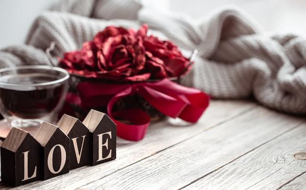 Feestelijk huisstilleven met houten woordliefde, een kopje thee en bloemen op een onscherpe achtergrond.